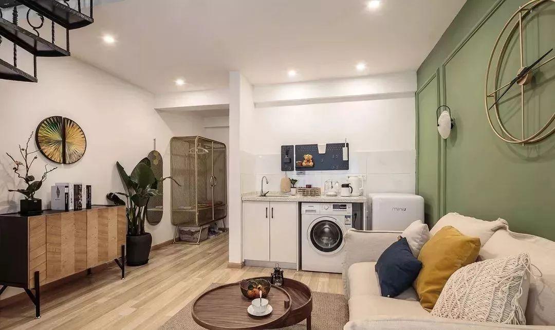 2玄关,玄关处摆放了一个金属质感的架子,上半部分可以挂衣服,下半部分可以收纳鞋子,旁边还有全身镜挂在墙上,也不占用多少空间,对面就是卫生间。从玄关进来就看到一字型开放式小厨房,冰箱还嵌入橱柜里,因为业主不经常做饭,所以这样的小厨房就够了。还有木质电视柜和绿植装饰,都很简约。.jpg