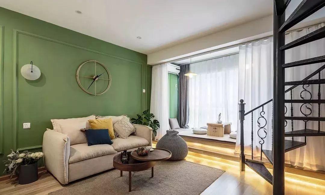 3客厅,沙发背景墙是复古一些的绿色,还做了石膏线装饰,简约却很有格调,搭配杏色的布艺沙发,还有小盆绿植装饰,整个客厅都自然清爽。.jpg