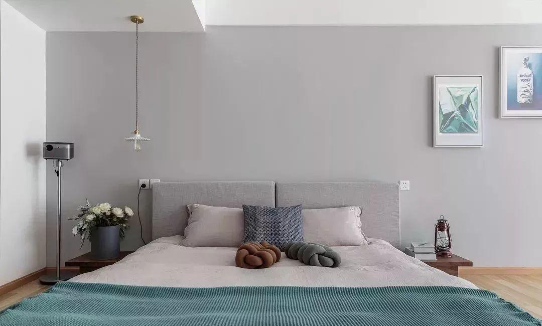 7床头背景墙刷成浅灰色的,垂下来一盏吊灯照明,床头两侧还有小巧的床头柜,床铺也是素雅的颜色,很舒服,也简约大方。.jpg
